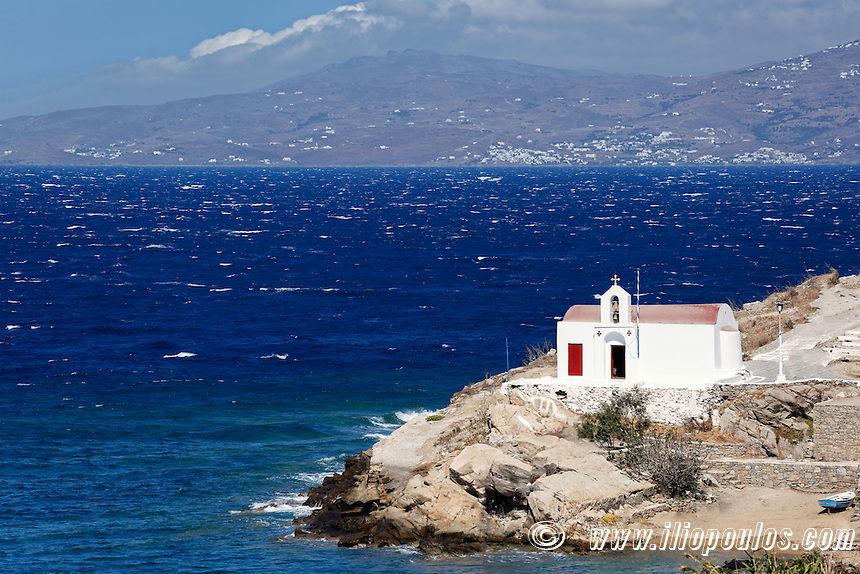 A small white chapel on a rocky coast of Chora in Mykonos, Greece