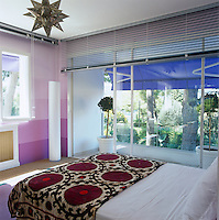 The bedroom has its own private covered balcony and the bed is covered in an antique suzani