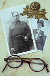 Vintage black and white photos of man in World War 2 army uniform and in civilian clothes lying with his spectacles and 8th Army badge