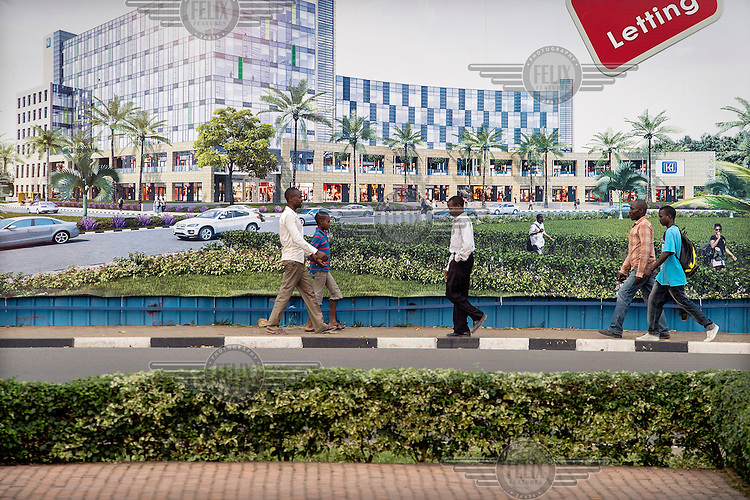 Pedestrians pass a billboard advertising a forthcoming shopping and office complex.