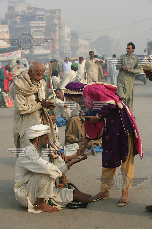 A begger receives some money from a woman on the streets of Lahore.