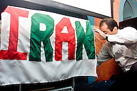 Ali Fare, a waiter at the Persian Tea Room (a restaurant in the New York City area), hangs up an Iran banner under a big screen television before the start of the Iran-Mexico match on June 11, 2006.<br /> <br /> The World Cup, held every four years in different locales, is the world's pre-eminent sports tournament in the world's most popular sport, soccer (or football, as most of the world calls it).  Qualification for the World Cup is open to any country with a national team accredited by FIFA, world soccer's governing body. The first World Cup, organized by FIFA in response to the popularity of the first Olympic Games' soccer tournaments, was held in 1930 in Uruguay and was participated in by 13 nations.    <br /> <br /> As of 2010 there are 208 such teams.  The final field of the World Cup is narrowed down to 32 national teams in the three years preceding the tournament, with each region of the world allotted a specific number of spots.  <br /> <br /> The World Cup is the most widely regularly watched event in the world, with soccer teams being a source of national pride.  In most nations, the whole country is at a standstill when their team is playing in the tournament, everyone's eyes glued to their televisions or their ears to the radio, to see if their team will prevail.  While the United States in general is a conspicuous exception to the grip of World Cup fever there is one city that is a rather large exception to that rule.  In New York City, the most diverse city in a nation of immigrants, the melting pot that is America is on full display as fans of all nations gather in all possible venues to watch their teams and celebrate where they have come from.