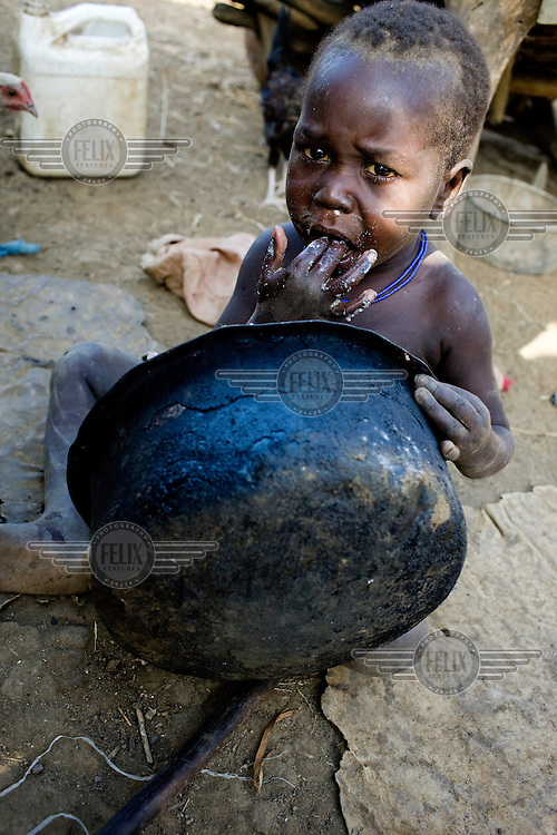 A young child scrapes out the cooking pot in order to get a little extra to eat.