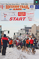 Musher Sebastian Schnuelle and Iditarider Tamara Balster-Hess leave the 2011 Iditarod ceremonial start line in downtown Anchorage, Alaska