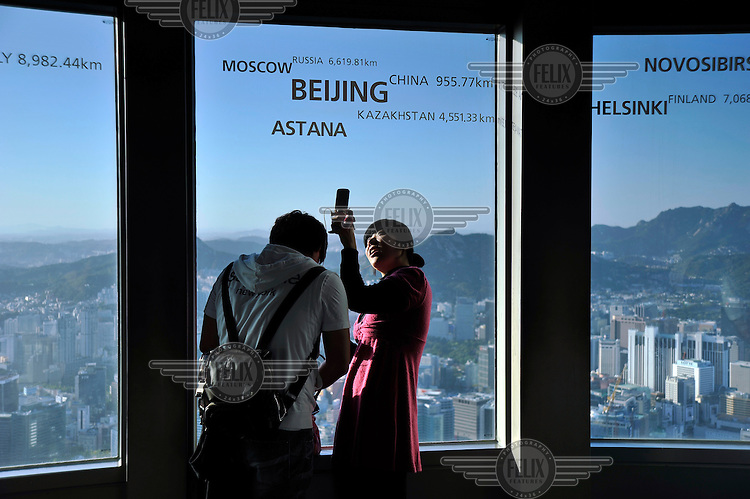 A couple take photographs fro the observation deck of the iconic Seoul Tower, rising from its park on a hill that dominates the capital.