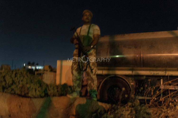 19/07/14  Iraq -- Daquq, Iraq -- A peshmerga fighter standing on the check point at the the night in the peshmerga base in Daquq.