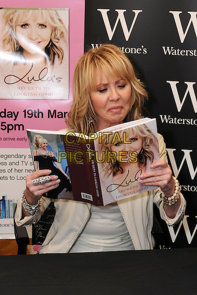 "LULU (Lulu Kennedy Cairns).Signs copies of her new book ""Lulu's Secrets To Looking Good"" at Waterstone's, Bluewater, Greenhithe, Kent, England, UK, 19th March 2010..half length  cream jacket top beads bracelets beige leather sitting down reading looking funny ring silver .CAP/BRC.©Ben Rector/Capital Pictures"