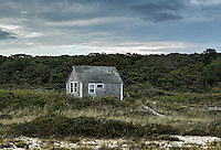 A remote coastal cottage weathered by wind and sea salt.