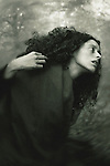 A woman in long black curly hair and a dark scarf on her shoulders, in a dramatic pose and with expression of grief or anxiety.