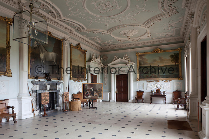 The grand hall of Badminton House in Gloucestershire which dates from the 17th century. A life size horse portrait by John Wootton hangs above the fireplace