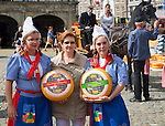A tourist with girls wearing national costume, Gouda and cheese market, South Holland, Netherlands,