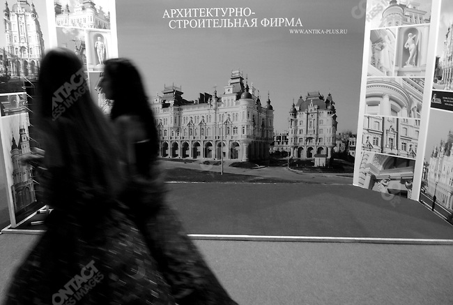 A pair of hostesses walked past a real estate stand selling chateau style houses at the Millionaire's Fair in Moscow. November 23, 2007