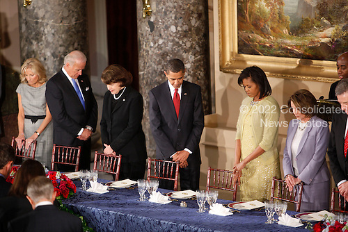 Washington, DC - January 20, 2009 -- United States President Barack Obama, center,with from left to right Jill Biden, Vice-President Joseph Biden, first lady Michelle Obama and Speaker of the House Nancy Pelosi (Democrat of California) hold their head down in prayer before lunch at Statuary Hall in the U.S. Capitol  in Washington, Tuesday, January 20, 2009. .Credit: Lawrence Jackson - Pool via CNP