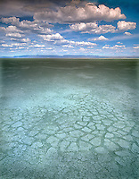 Dry Summer Lake bed in summer with puffy clouds. Oregon