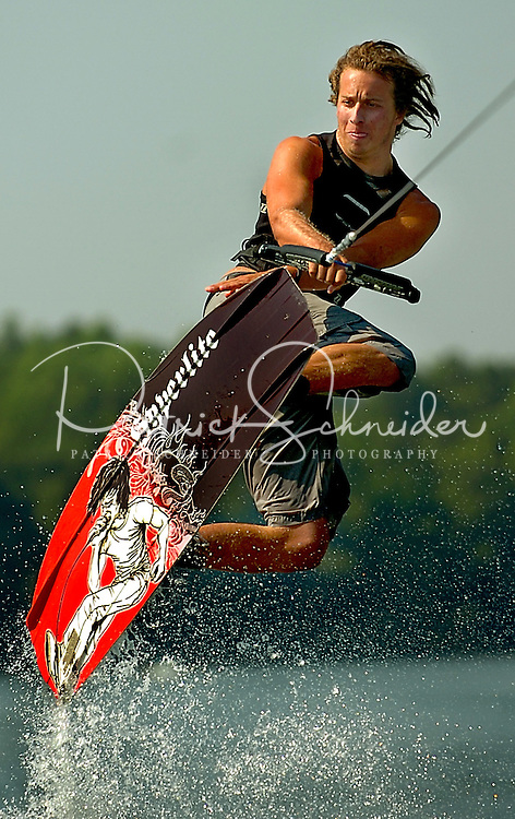 Aaron Tompkins, 19, flies thru the air on his wakeboard,  on Davidson Lake in Cornelius, NC. Tompkins, a wakeboard instructor at the Camp Lake Land at Lake Norman YMCA, was showing his campers the proper way to get some great height off the wakes on the lake.