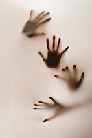 Two pair of hands partially silhouetted behind translucent fabric