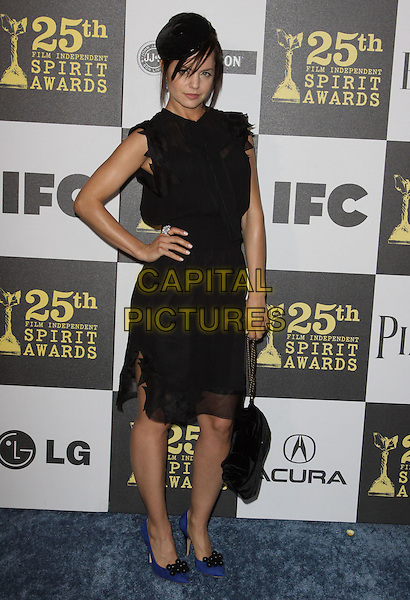 MENA SUVARI .25th Annual Film Independent Spirit Awards held At The Nokia LA Live, Los Angeles, California, USA,.March 5th, 2010 ..arrivals Indie Spirit full length black ruffle trim ruffle sheer see thru through dress hat sleeveless blue pointy shoes heels bag hand on hip .CAP/ADM/KB.©Kevan Brooks/Admedia/Capital Pictures