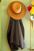 Still life of straw hat and coat hanging on coat hook. Strasburg Pennsylvania USA Lancaster County.