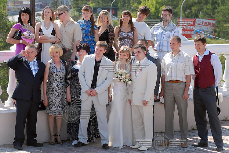 Wedding photographs are taken of the married couple and their guests in the city of Krasnoyarsk.