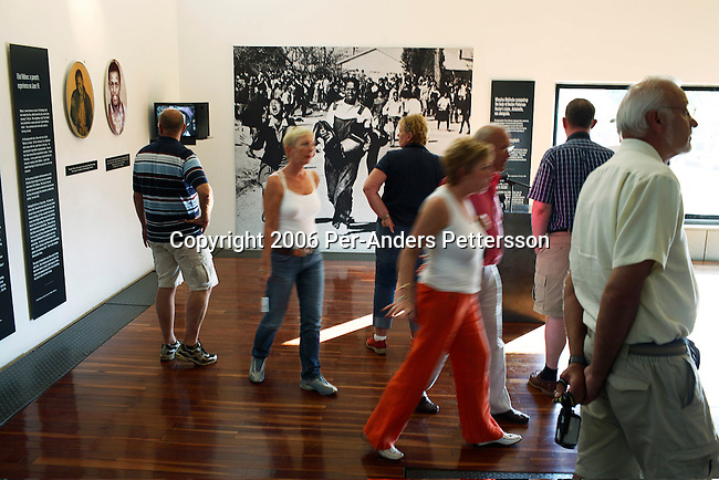 SOWETO, SOUTH AFRICA OCTOBER 23: Foreign tourists look through the Hector Pieterson Museum on October 23, 2006 in Soweto, Johannesburg, South Africa. The museum has exhibitions and media show of the struggle against Apartheid in the country. Soweto is South Africa?s largest township and it was founded about one hundred years to make housing available for black people south west of downtown Johannesburg. The estimated population is between 2-3 million. Many key events during the Apartheid struggle unfolded here, and the most known is the student uprisings in June 1976, where thousands of students took to the streets to protest after being forced to study the Afrikaans language at school. Soweto today is a mix of old housing and newly constructed townhouses. A new hungry black middle-class is growing steadily. Many residents work in Johannesburg, but the last years many shopping malls have been built, and people are starting to spend their money in Soweto.  .(Photo by Per-Anders Pettersson/Getty Images).