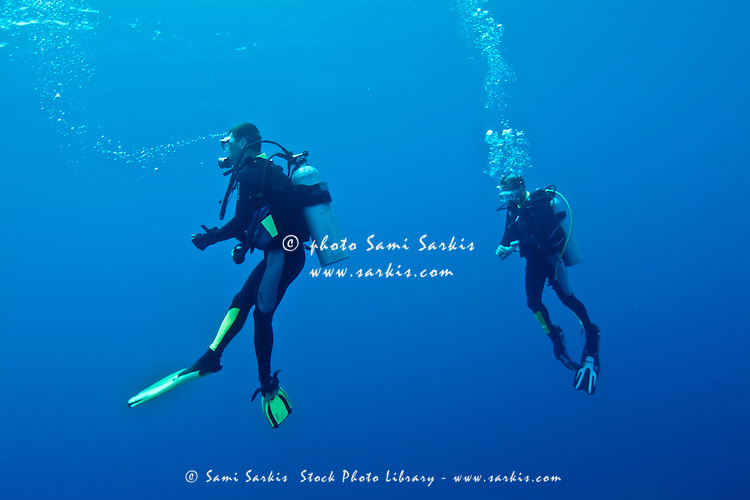 Two scuba divers searching for a giant manta ray near the Kaafu Atoll, Maldive Islands.