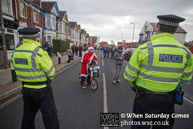 "Portsmouth 1 Southampton 1, 18/12/2012. Fratton Park, Championship. A woman on a bicycle dressed in a Father Christmas suit waiting to cross a line of police officers in a closed-off street outside Fratton Park stadium before Portsmouth take on local rivals Southampton in a Championship fixture. Around 3000 away fans were taken directly to the game in a fleet of buses in a police operation known as the ""coach bubble"" to avoid the possibility of disorder between rival fans. The match ended in a one-all draw watched by a near capacity crowd of 19,879. Photo by Colin McPherson."