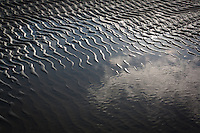 Ripples on a beach left by the falling tide. Studland, Dorset, UK.