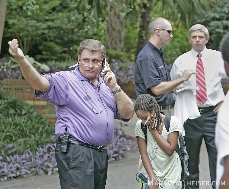 Cobb Middle School principal Bob McDaris, left, signals a replacement school bus while assisting one of his students Kanyra Johnson, 11 years-old, while Tallahassee Police Department officers talk with Leon County School superintendent Jackie Pons after a Leon County School bus carrying 42 Cobb students collided with a pick up truck at the intersection of 7th Ave and Mitchell St. in Tallahassee, Florida  September 14, 2007.  (Mark Wallheiser/TallahasseeStock.com)