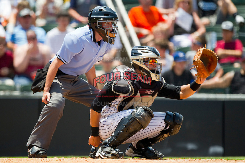Catcher Kevin Dubler #27 of the Kannapolis Intimidators sets a target as home plate umpire Andy Draper looks over his shoulder during the South Atlantic League game against the Hagerstown Suns at Fieldcrest Cannon Stadium on May 30, 2011 in Kannapolis, North Carolina.   Photo by Brian Westerholt / Four Seam Images