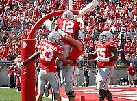 Teammates congratulate Ohio State Buckeyes quarterback Cardale Jones (12) after he ran for a touchdown during the third quarter of the NCAA football game at Ohio Stadium in Columbus on Sept. 21, 2013. (Adam Cairns / The Columbus Dispatch)