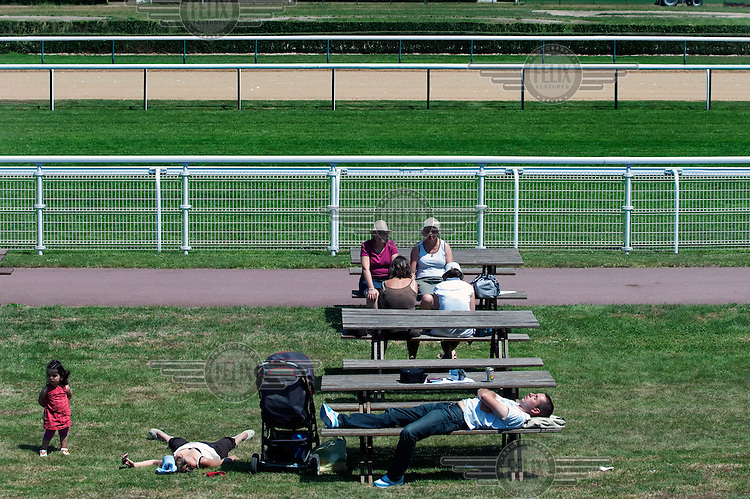 People relax at picnic tables at a racecourse in Deauville.
