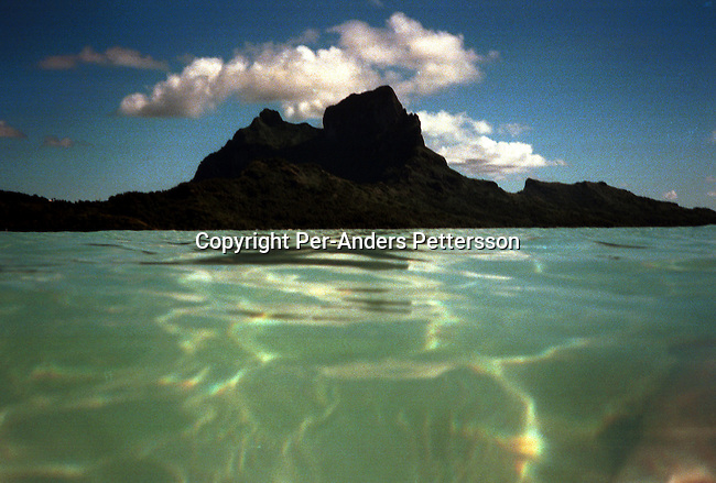 A view of the clean water and a mountain on April 16, 1997 on Bora Bora, a paradise island in French Polynesia. The Island is a playground for rich tourists and Hollywood stars as it provides total security and privacy. Most local people live of the tourism industry usually working in one of the luxury resorts. .(Photo: Per-Anders Pettersson/ Getty Images)