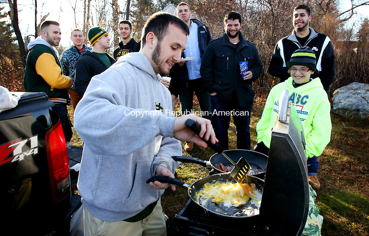 WOLCOTT CT. 26 November 2015-112615SV02-Anthony Lucia of Waterbury cooks for fellow Holy Cross graduates as Logan Bessette, 11, of Waterbury waits for breakfast before the annual Holy Cross Wolcott football game in Wolcott Thursday.<br /> Steven Valenti Republican-American