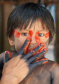 Aldeia Baú, Para State, Brazil. Mothe paints urucum red on her son before entering the forest.