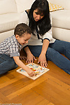 2 year old toddler boy doing puzzle assisted by mother