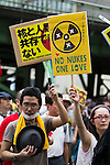 August 6, 2011 - Tokyo, Japan - Protestors holds anti-nuclear messages as they march past the TEPCO headquarters in downtown Tokyo. August 6 marks the 66th anniversary of the US atomic bombing of Hiroshima in 1945 as Japan still continues to struggle to end the nuclear crisis since the March 11 earthquake and tsunami. (Photo by Christopher Jue/AFLO)