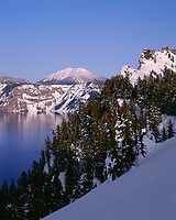 67ORCL_10 - USA, Oregon, Crater Lake National Park, Evening light warms snowy rim of Crater Lake in late afternoon and distant Mount Scott.