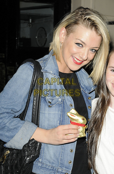 "SHERIDAN SMITH .Seen leaving after the evening performance of ""Flare Path"", Theatre Royal Haymarket, London, England, UK, April 22nd 2011..half length denim jacket black  smiling easter lindt gold bunny egg holding chocolate .CAP/CAN.©Can Nguyen/Capital Pictures."
