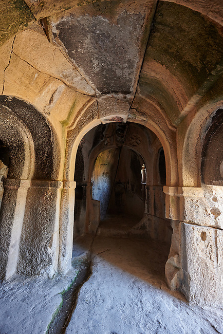 "Pictures & images of Kalburlu (St. Epthemios) church interior, 9th century, the Vadisi Monastery Valley, ""Manastır Vadisi"",  of the Ihlara Valley, Guzelyurt , Aksaray Province, Turkey.<br /> <br /> Kalburlu (St. Epthemios) church dates back to the 9th or 10th century. It is carved out of a single rock massive with rock columns holding up the roof of its church . The arches of Kalburlu (St. Epthemios) church have rich architectural decorated relif sculptures. The naves are connected by rounded arches & there is a baptismal font to the east of the main entrance."