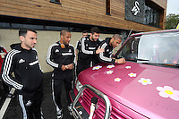 Pictured L-R: Players Leon Britton, Wayne Routledge, Jordi Amat and Ashley Williams sign the Suzuki Samurai at the Landore Training Ground. Saturday 10 May 2014<br />