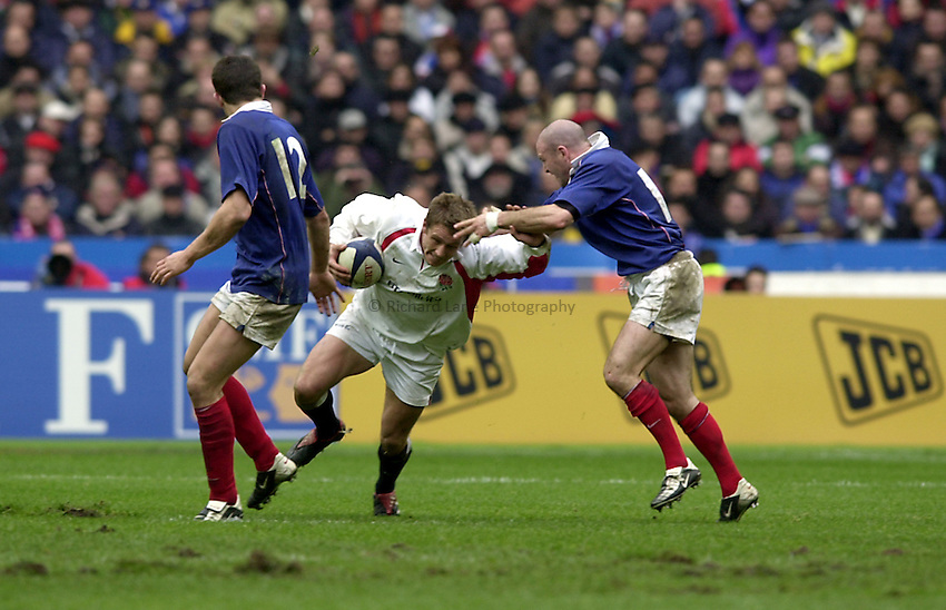 Photo.Richard Lane.France v England at Stade de France. 2-3-2002. Lloyds TSB Six Nations Championship..Jonny Wilkinson ducks Gerald Merceron's tackle.