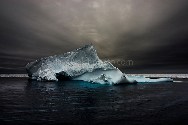 Formerly part of a tabular ice shelf,  an iceberg slumps into the Southern Ocean. Antarctica, 2007<br />