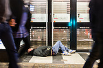 © Joel Goodman - 07973 332324 . No syndication permitted . 01/01/2014 . Manchester , UK . A man lies collapsed in a shop doorway . Revellers see in the New Year in Manchester today (January 1st 2014) as police report that officers are at full stretch responding to calls . Photo credit : Joel Goodman