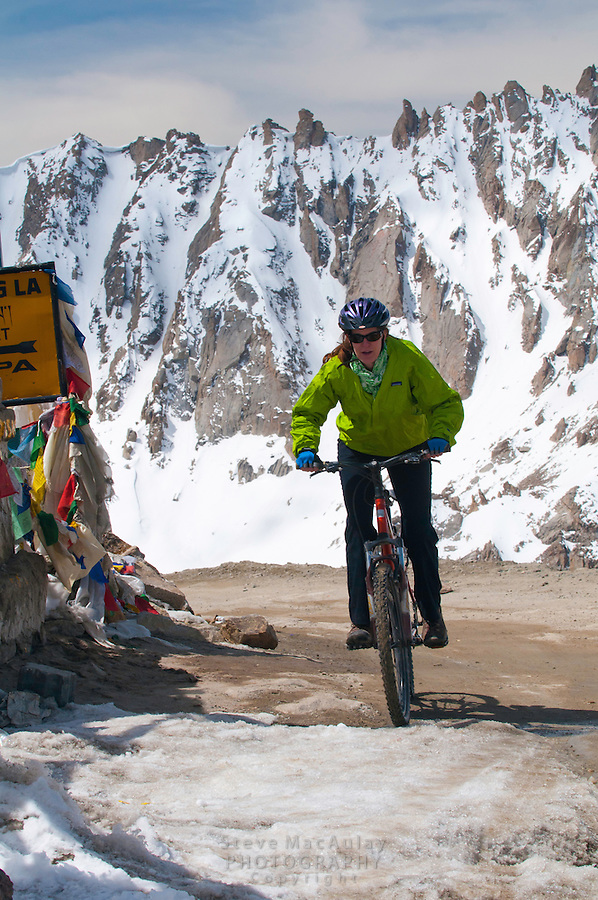 Mountain biker at Khardung La, at 18,380ft, the summit of the highest motorable road in the world,  Himalayan Mountains, Ladakh, India.
