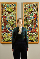 BNPS.co.uk (01202 558833)<br /> Pic: ZcharyCulpin/BNPS<br /> <br /> Pictured: Emma Rowland from the Russell-Coates Art Gallery with a stunning Scarlet Macaw and Blue Fronted Parrot Tile panel. The complex pattern repeats over 18 tiles before being reflected over a further 18. The tile panel would have been used to cover interior walls.<br /> <br /> 'Sublime Symmetry' at Russell-Coates Art Gallery and Museum in Bournemouth, Dorset<br /> <br /> The Sublime Symmetry exhibition showcases the work of William De Morgan. The celebrated Arts and Crafts designer (1939-1917) was seen as the most inventive ceramic designer of the Victorian period.  The exhibition which runs until the 2nd February explores the Mathematics behind De Morgan's Ceramic designs.