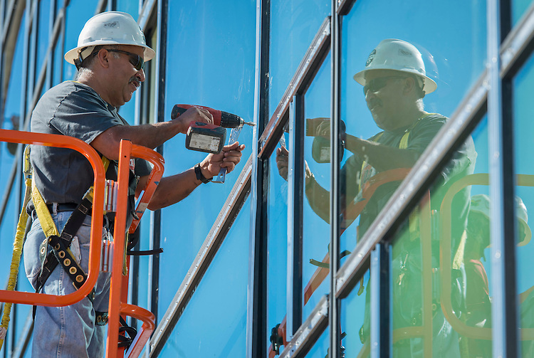 Workmen install windows at Waltrip High School, January 28, 2015.
