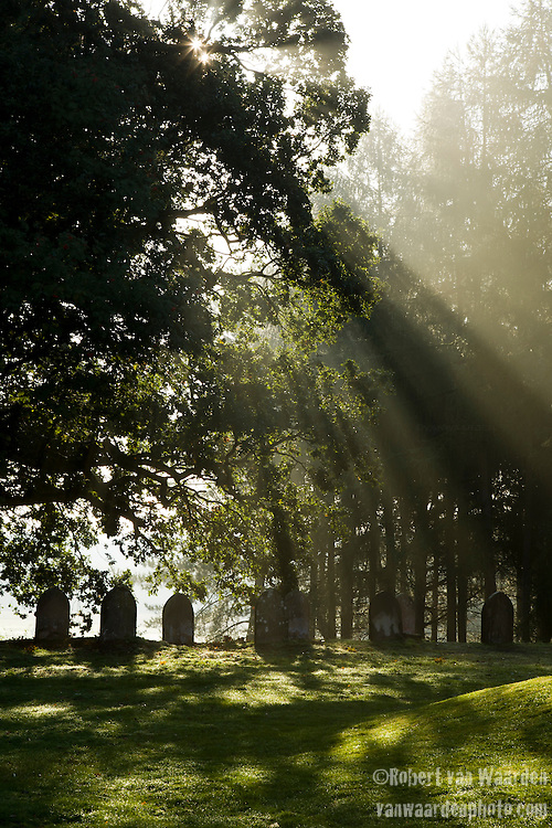 Early morning light rays on a cemetary on the Shuttleworth estate at Old Warden, Bedfordshire, the United Kingdom.