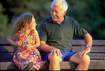 elder man conversing with young girl on park bench