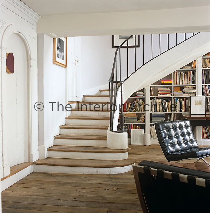 A sweeping staircase rescued from a salvage yard contrasts elegantly with the Barcelona chairs and other iconic 20th century furniture in this open-plan living area