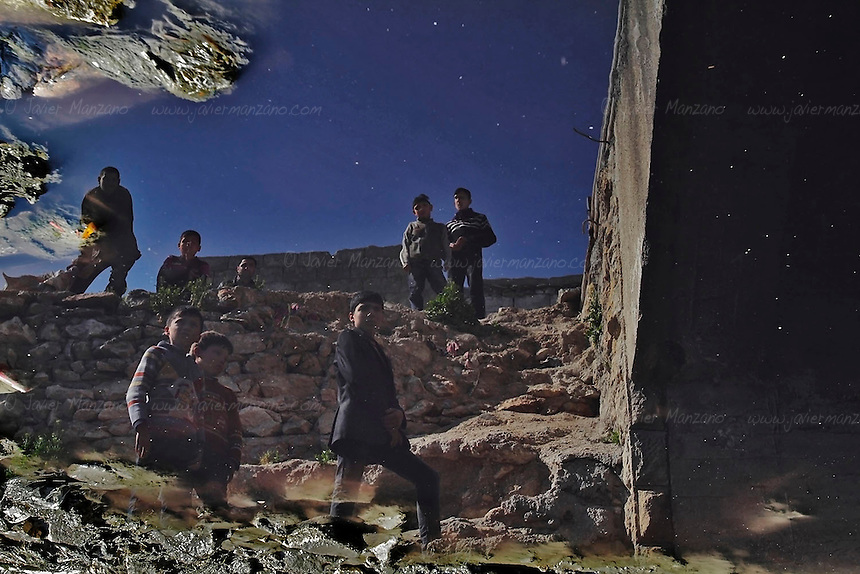 "The reflection of onlookers who regularly visit the ""River of Martyr's"" (the name given to the Qweiq river that divides most of the rebel-controlled sections of Aleppo from the regime strongholds in the city ) gather to see if any bodies have washed up under a bridge. The river was renamed earlier this year after 110 bodies washed up in January. Most of them showed signs of torture and almost all of them were executed with their hands bound behind their backs. Hundreds of people claim to have missing relatives, most of whom disappeared in the regime-controlled areas of the city, as work and commerce are only found in these areas. Everyday, thousands of civilians who live in the Free Syria Army side of the city travel to the regime areas to work (or to seek employment). Dozens are shot by regime snipers while commuting to and from the government controlled areas of the city. Some do not return at all. Every morning, dozens of civilians walk down to the banks of the canal to see if there are any new bodies washing up. For some, this is their daily routine - the daily stroll to the water canal in search of the body of their missing loved ones."